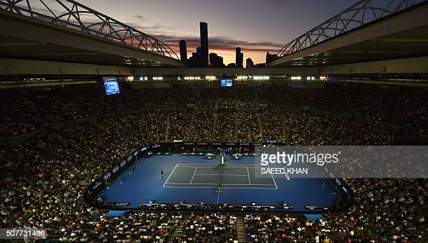 TOPSHOT Sun sets over the skyline as Britain's Andy Murray plays during his men's singles final match against Serbia's Novak Djokovic on day fourteen...