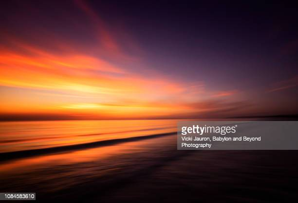sun setting against soft waves and dramatic colors at fort myers beach, florida - fort myers beach stock pictures, royalty-free photos & images