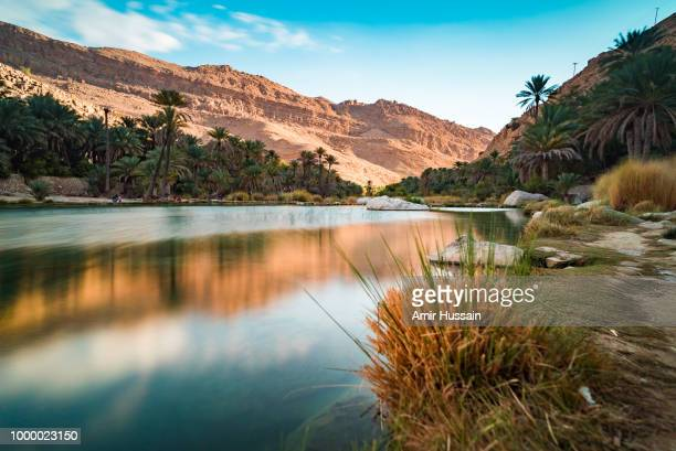 sun setting at wadi bani khalid - oman fotografías e imágenes de stock
