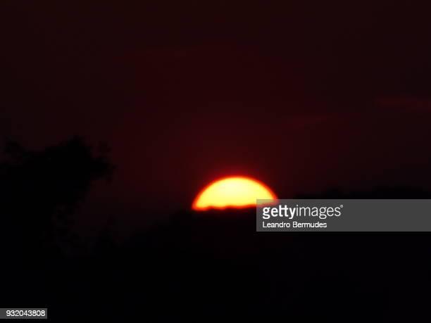 Sun setting behind a mountain.
