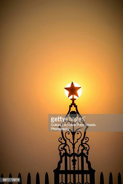 Sun setting behind a star on the presidential palace in Delhi, India