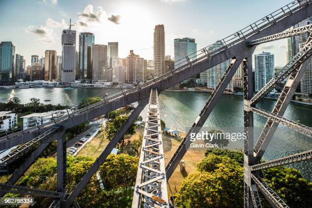 sun setting behind brisbane skyline - brisbane stock photos and pictures