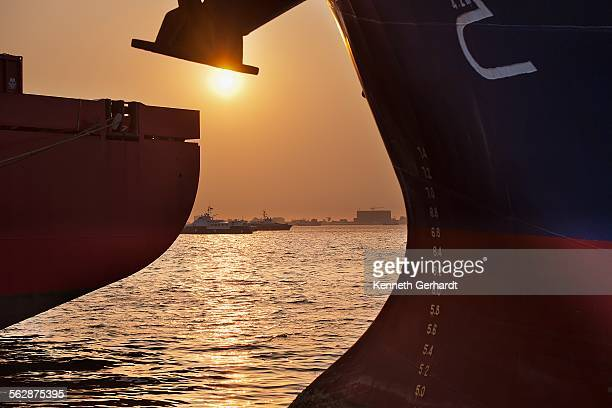 sun setting behind cargo vessel, angola, luanda bay - angola stock pictures, royalty-free photos & images