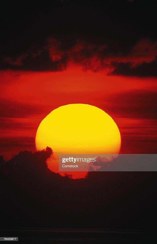 Sun setting behind clouds : Stockfoto