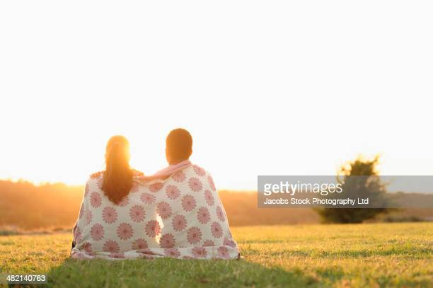 Sun setting behind couple wrapped in blanket in field