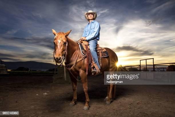 Sun Setting Behind Cowboy on Horseback