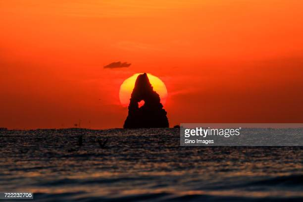 Sun setting behind rock standing out from sea, Qingdao, Shandong, China