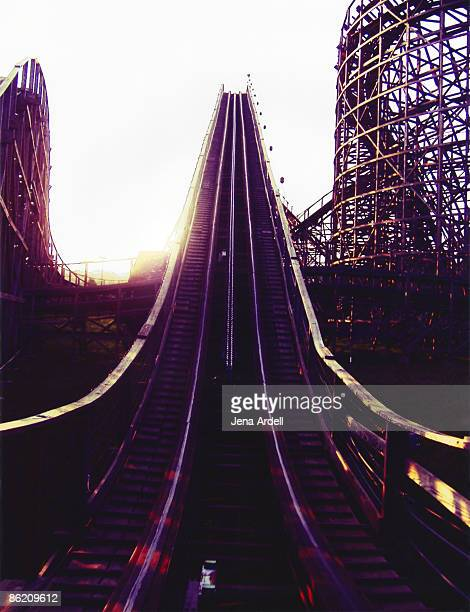 Sun setting behind wooden roller coaster tracks