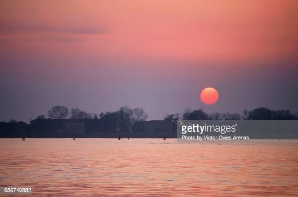 sun setting behing san servolo island on the venetian lagoon from venice lido (lido di venezia) in venice, italy - victor ovies fotografías e imágenes de stock