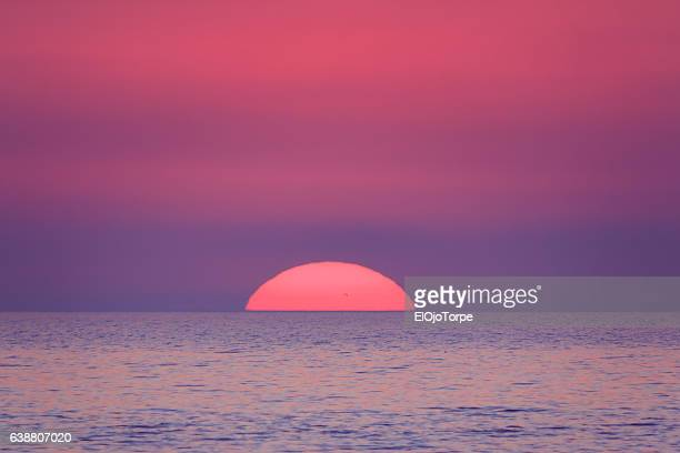 sun setting in atlantic ocean, view from piriápolis beach, uruguay - rose colored stock pictures, royalty-free photos & images