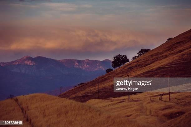 sun setting on high sierra nevada mountains beyond foothills near springville, california - springville california stock pictures, royalty-free photos & images