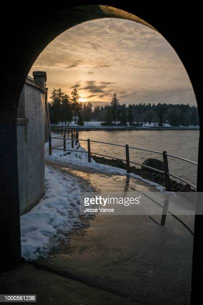sun setting on the seawall. - seawall stock pictures, royalty-free photos & images