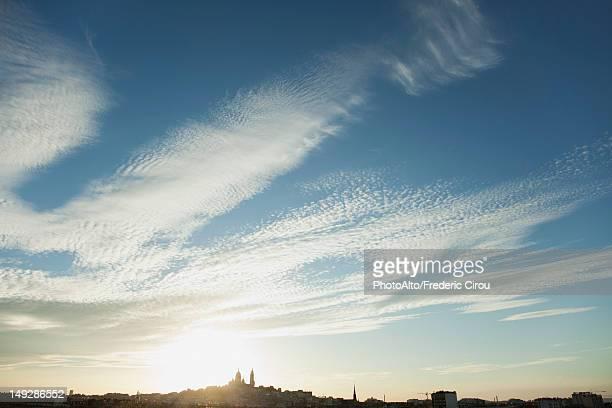 Sun setting over distant skyline of Paris, France