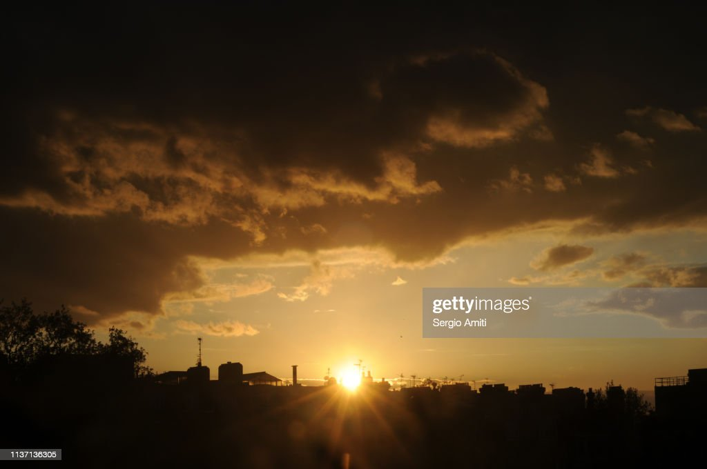 Sun setting over houses in London : Stock Photo
