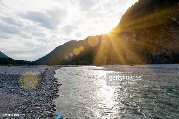 sun setting over rocky river - fiume isar foto e immagini stock