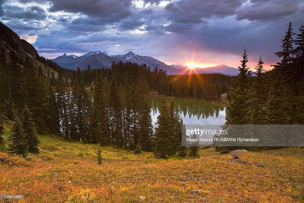 Sun setting over still rural lake : Stock Photo