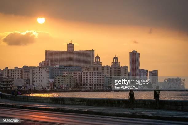 Sun setting over the Edificio Focsa from the Malecon with silhouettes Havana