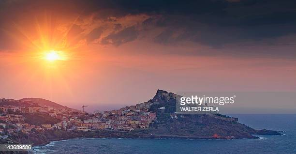 Sun setting over village on hillside