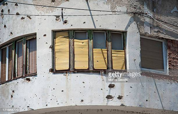 Sun shines on a window and a concrete wall damaged by bulletts from the 1993 war as the city of Mostar remembers the 1993 conflict on June 28, 2013...