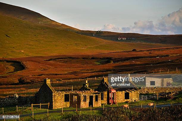 Sun shines on an old building and telephone box on the Island of Foula on October 2 2016 in Foula Scotland Foula is the remotest inhabited island in...