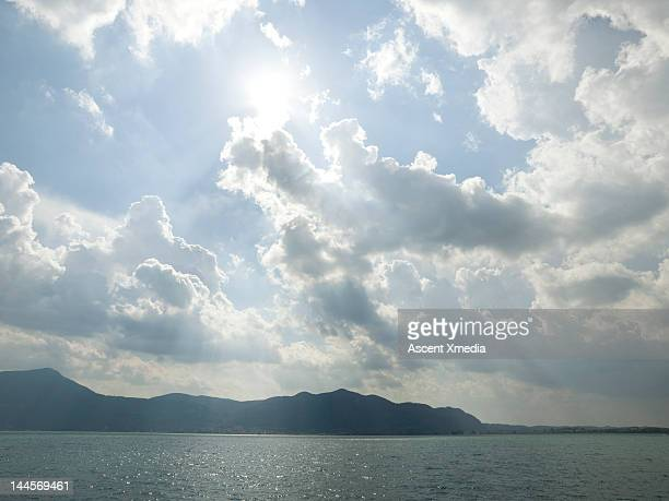 sun shines through clouds above a mountain lake - number of people stock photos and pictures