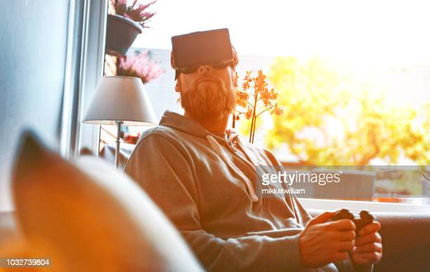 Sun shines through windows to a living room where man with headset plays a virtual reality game