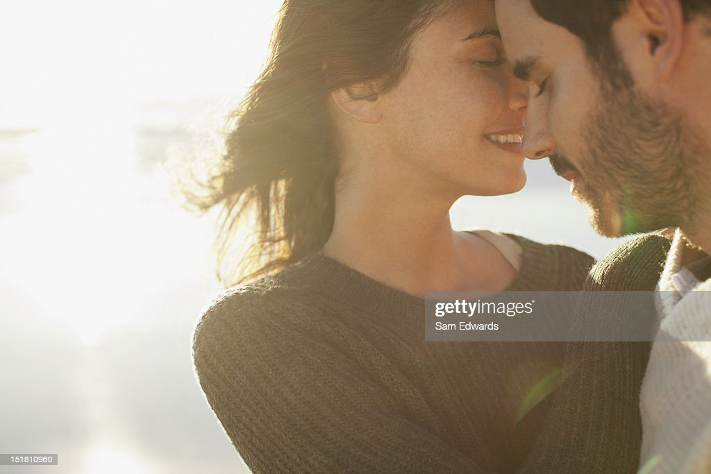 Sun shining behind couple hugging with eyes closed : Stock Photo