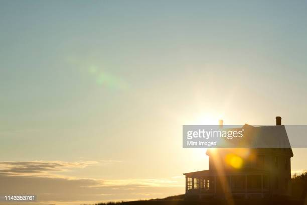 sun shining behind rural house - morning stock pictures, royalty-free photos & images