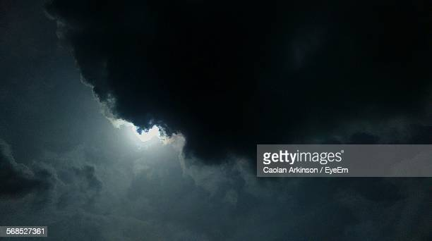 sun shining behind stormy clouds - storm cloud stock pictures, royalty-free photos & images