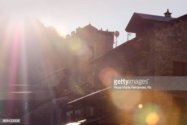 Sun shining in between tipical houses in beautiful town at dawn,  Broto, Huesca, northern Spain.