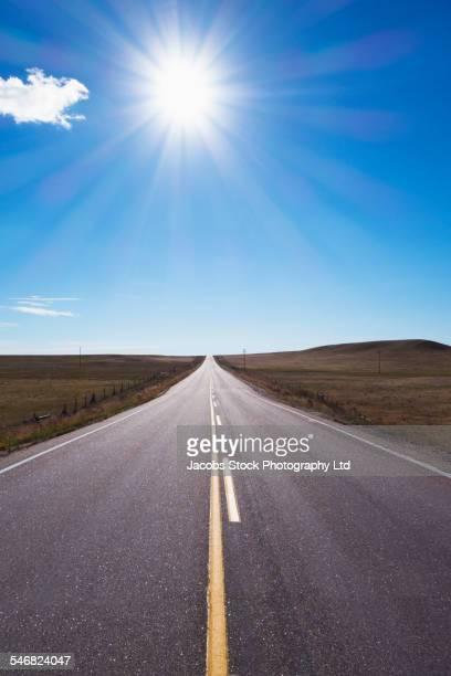 Sun shining in blue sky over empty rural road