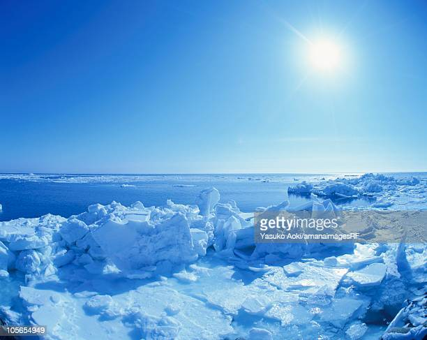 sun shining in the sky above piles of drift ice. hokkaido, japan - drift ice stock pictures, royalty-free photos & images