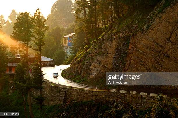 sun shining on curvy road - punjab pakistan stock photos and pictures