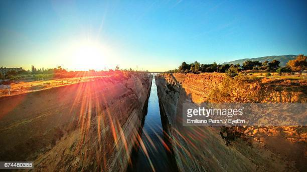 sun shining over corinth canal - peloponnese stock photos and pictures