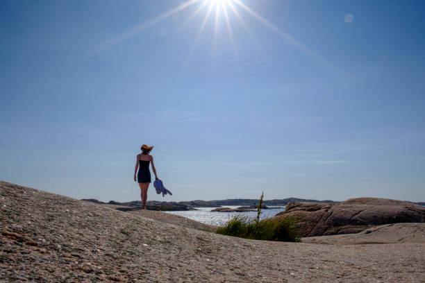 Sun shining over teenage girl walking alone along rocky shore