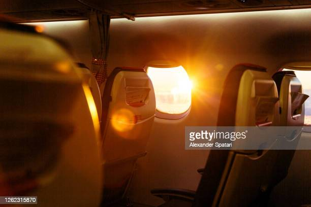 sun shining through airplane window at sunrise - vehicle seat stock pictures, royalty-free photos & images