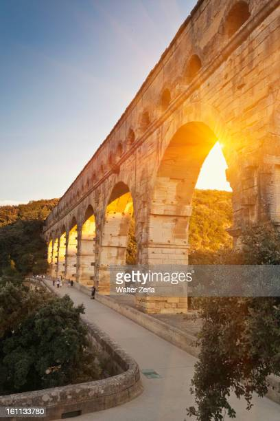 sun shining through aqueduct - pont du gard stockfoto's en -beelden