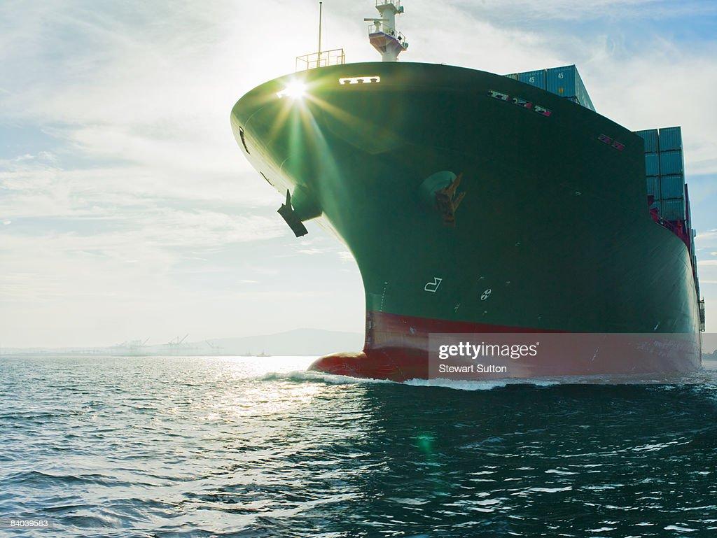 Sun shining through bow of cargo ship : Stock Photo