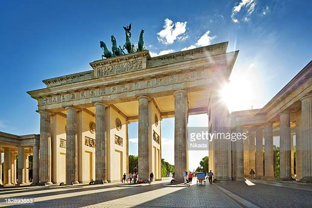sun shining through brandenburg gate in berlin - berlin stock pictures, royalty-free photos & images