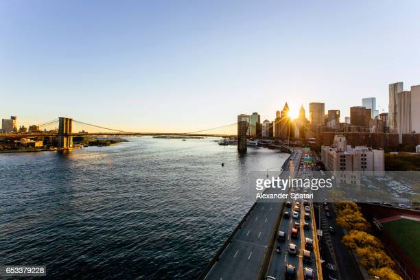 Sun shining through Brooklyn bridge and skyscrapers of Downtown District of Manhattan, New York, USA