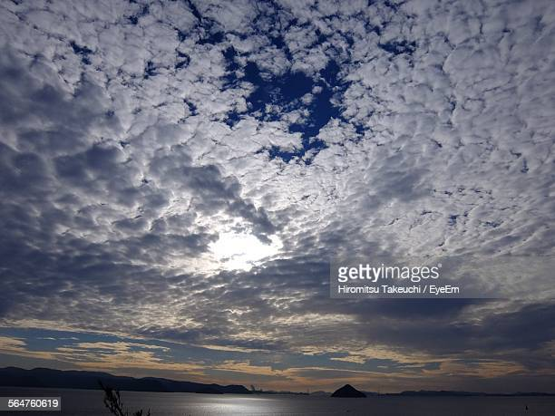 sun shining through clouds over sea - altocumulus stockfoto's en -beelden