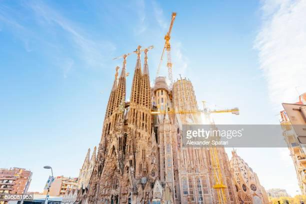sun shining through nativity facade of sagrada familia, barcelona, spain - sagrada familia stock pictures, royalty-free photos & images