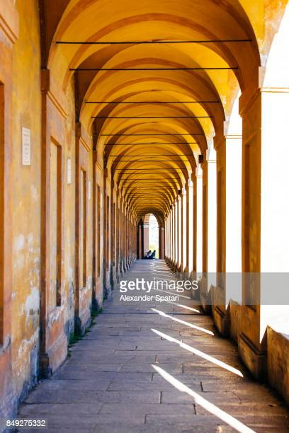 Sun shining through portici (arches) in Bologna, Emilia-Romagna, Italy