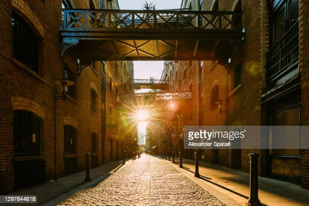 sun shining through shad thames street during sunset, london, uk - shiny stock pictures, royalty-free photos & images