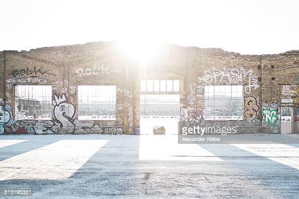 Sun shining trough Street Art brick wall in Berlin