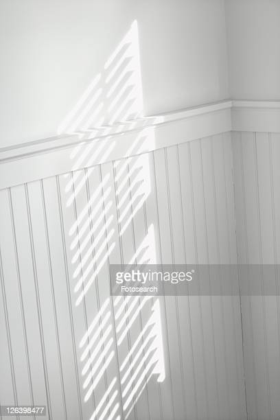 Sun spot on wall from light shining through window blinds.