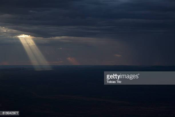 Sun streaming through storm clouds on landscape