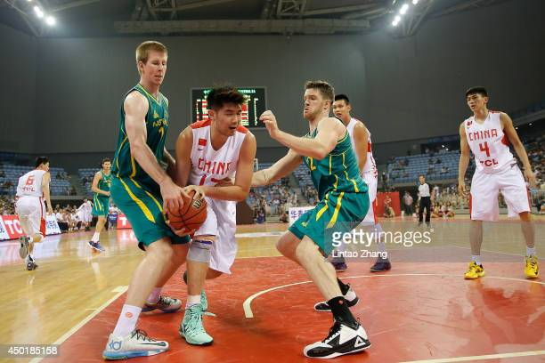 Sun Tonglin of China drives to the basket against Brock Motum and Lucas Walker of Australia during the 2014 Sino-Australia Men's International...