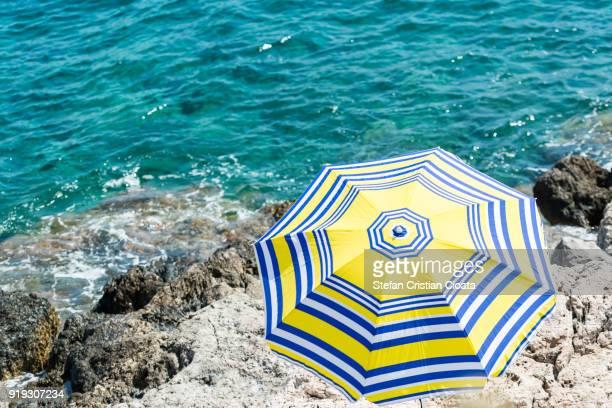 sun umbrella on greece shore - peloponnese stock photos and pictures