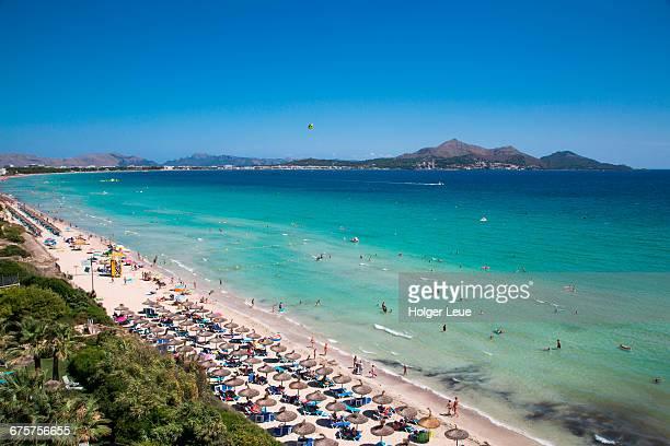 sun umbrellas and people on playa de muro beach - majorca stock pictures, royalty-free photos & images